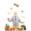 A smiling mature man juggling fruits behind a table full with fr
