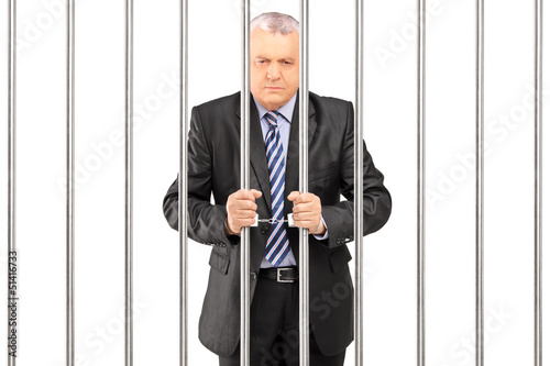 A handcuffed manager in suit posing in jail and holding bars