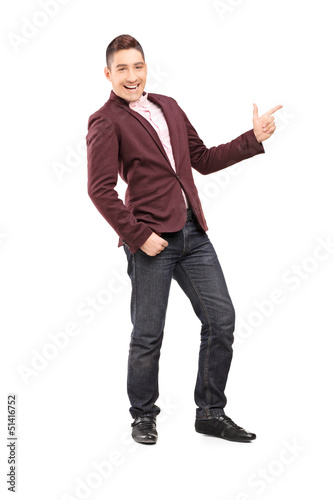 Full length portrait of a fashionable smiling guy pointing with