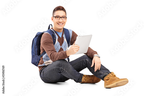 Smiling male student with backpack seated on a floor holding a t