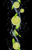 Fototapety Limes in water splash, isolated on black background