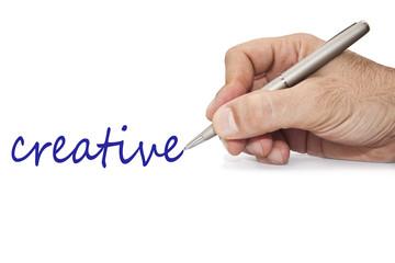 mano con boli escribiendo la palabra creativo