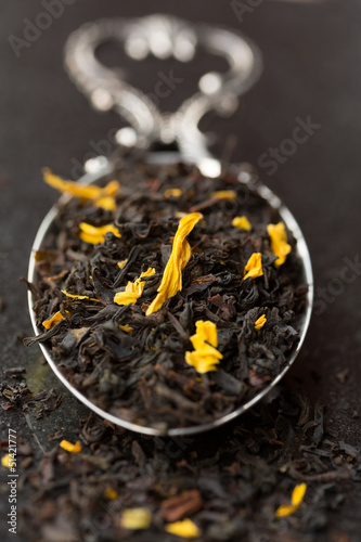 Black tea leaves with flowers on tea spoon