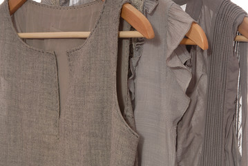 Grey dresses are on wooden hangers.
