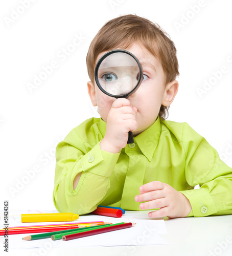 Cute little boy is playing with magnifier