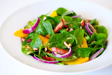 Spinach salad with mango, ham, onion and almonds