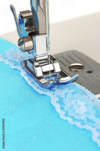 Closeup of sewing machine working part with  blue cloth