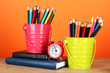 Colorful pencils in two pails with writing-pad