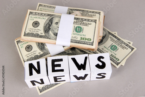 "White paper cubes labeled ""News"" with money on grey background"