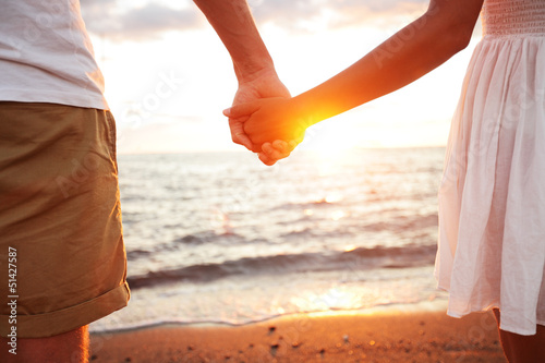Summer couple holding hands at sunset on beach