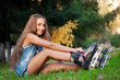 girl sitting on the grass and puts on skates