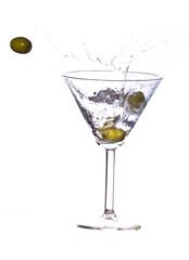 Olive splashing on martini isolated on white