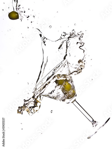Olive splashing on martini isolated on white