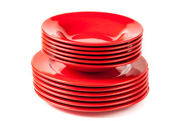 Stack of colorful red ceramics plates on white background