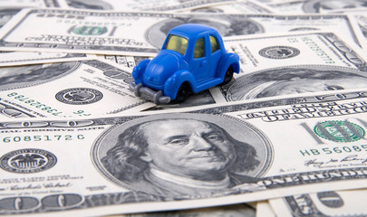 A toy car on a hundred dollar bill.