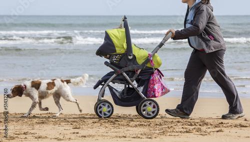 Madre con cochecito bebe por la playa