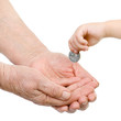 hands of the child put a coin in a palm of the old person