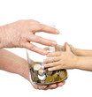 hands elderly and kids over to glass jar with coins