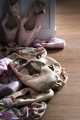 Group of pointe shoes on wooden floor