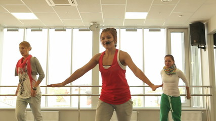 Smiling women and  trainer with headset dancing aerobics