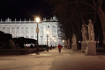 Alley and statues near majestic Royal Palace at night in Madrid,