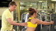 Personal trainer helping exercise to woman on sport machine