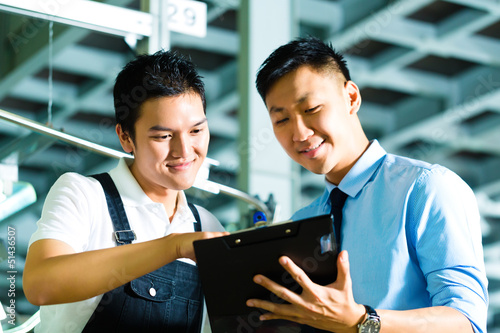 Worker and production manager with Clipboard