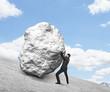 businessman pushing stone