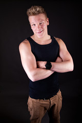 Muscular sexy smiling young cute man posing in a vest