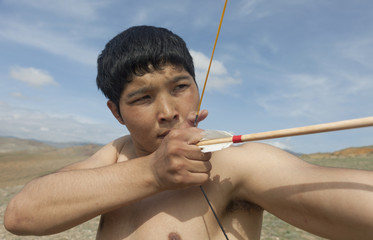 A young man shoots a bow