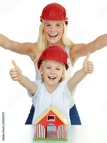 Two girls with helmet show thumbs up for building a house