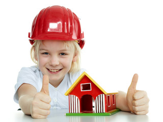 Little girl with helmet shows thumb up for building a house