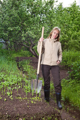 The young woman digs up a garden-bed with the first sprouts