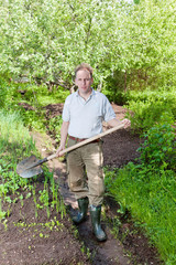 Man digs up a garden-bed with the first sprouts