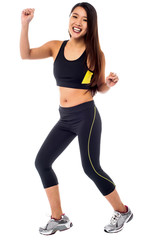 Cheerful fitness trainer dancing in joy