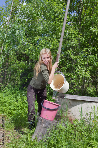 The young woman at a well, pours water in a bucket..