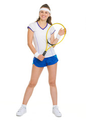 Full length portrait of smiling female tennis player with racket