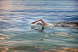 young sporting man swims in the sea