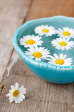 Spa setting with daisies in turquoise bowl