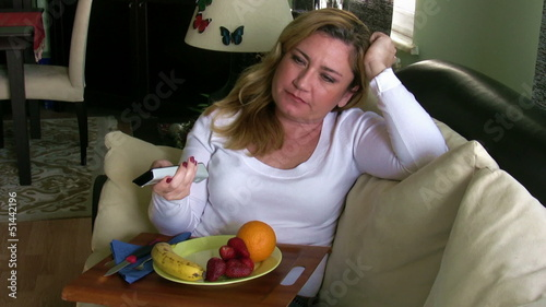 Woman watching tv and eating fruit