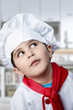 Funny boy dressed in chef, cooking in a kitchen