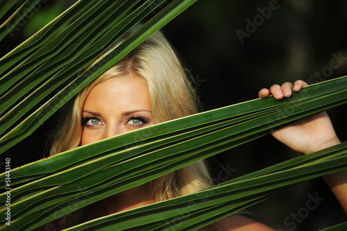 woman behind the palm leaves