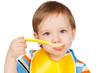 Boy eats with a spoon puree, isolated on white