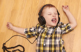 3 years old child listening music in headphones