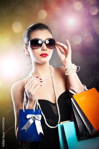 Beauty  young woman in sunglasses carrying colored shopping bag