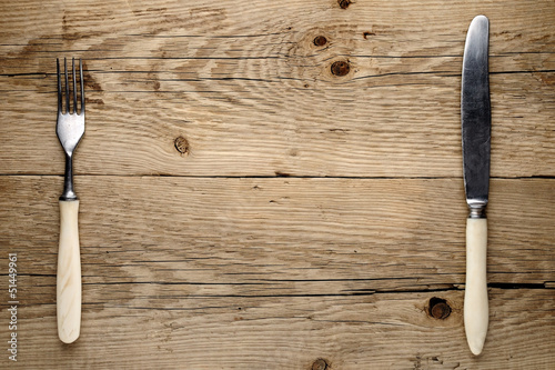 Old fork and knife on wooden background
