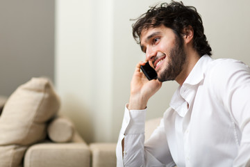 Young man smiling and talking on smart phone at home