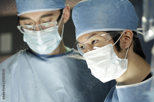 Asian surgeon working with assistant in surgery
