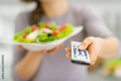 Closeup on tv remote control and salad in hand of young woman