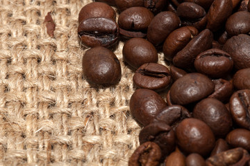 Coffee grains on rough fabric of linen close-up